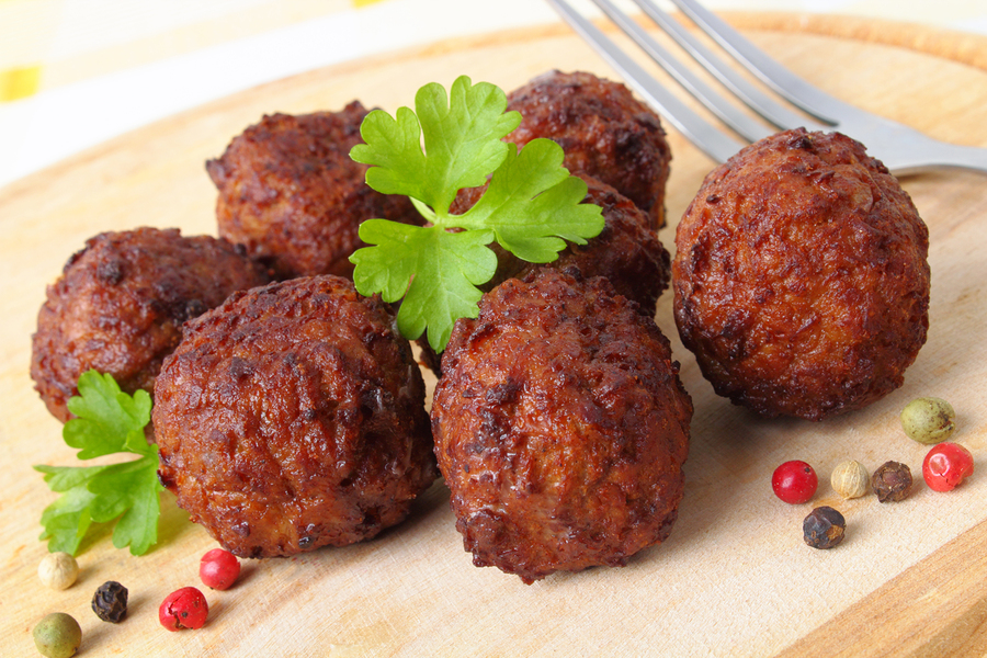 meatballs with pepper and parsley on a wooden board.